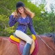 Young girl riding a horse. - Stock Photo