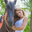 Portrait of a young girl with a horse. Focus on horses face. - Stock Photo