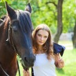 Young girl walking with a horse in the garden. - Stock Photo