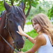 Young girl to train a horse.Focus on horses face. - Stock Photo