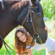 Stock Photo: Young girl playing with her horse.