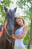 Portrait of a young girl with a horse. Focus on horses face. — Stock Photo