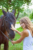 Young girl to train a horse.Focus on horses face. — Foto de Stock