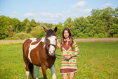 A young girl dressed as an Indian with a paint horse — ストック写真