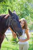 Young girl walking with a horse in the garden. — Stock Photo