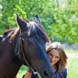 Portrait of a young girl with a horse. - Stock Photo