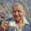 Stock Photo: Smiling elderly womdrinking coffee on background of floweri