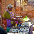 SIOLIM, GOA, INDIA - CIRCA DECEMBER 2013: An elderly woman sells — Stock Photo #39166901