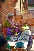 SIOLIM, GOA, INDIA - CIRCA DECEMBER 2013: An elderly woman sells — Foto de Stock