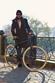 A young man stands on the promenade with the bike — ストック写真