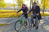 Young couple riding a bicycle in autumn park — ストック写真