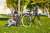 Young man reading a book in autumn park. — Stockfoto