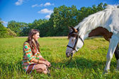 A young girl dressed as an Indian walking with a paint horse — Stock Photo