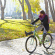 Stock Photo: A young girl learns to ride a bicycle in autumn park. Backlight.