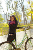 Young beautiful girl walking in autumn park on a bicycle — Stock Photo
