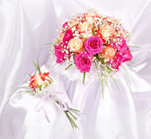 Wedding boutonniere and bridal bouquet on white silk background — Stock Photo