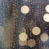 Rain on window with abstract lights — Stock Photo
