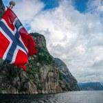 Norwegian flag against fjord mountains — Stock Photo