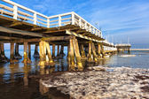 Snow pier in the sea on a sunny winter day. — Стоковое фото