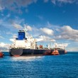 Tugboat towing a tanker — Stock Photo