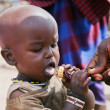 Maasai child trying a lollipop in Tanzania, Africa — ストック写真