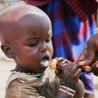 Maasai child trying a lollipop in Tanzania, Africa — Stockfoto