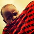 Maasai baby carried by his mother in Tanzania, Africa — Stock Photo