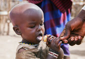 Maasai child trying a lollipop in Tanzania, Africa — Stock Photo