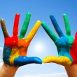 Painted hands, colorful fun. blue sky — Stock Photo #23361382