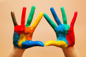 Painted hands, colorful fun. Orange background — Stock Photo