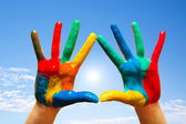 Painted hands, colorful fun. blue sky — Stock Photo