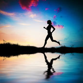 Silhouette of woman running at sunset — Stock Photo