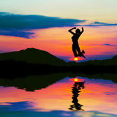 Silhouette of happy woman jumping at sunset — Stok fotoğraf