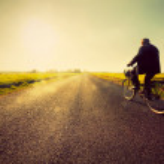 Old man riding a bike to sunny sunset sky — Stock Photo
