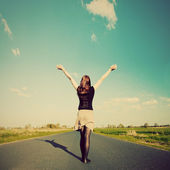 Happy woman standing on empty road. Retro vintage style — Stock Photo