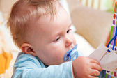 Young baby boy with a dummy in his mouth — Stock Photo