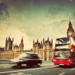 London, the UK. Red bus, taxi cab in motion and Big Ben — Stock Photo