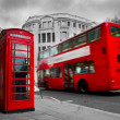 London, the UK. Red phone booth and red bus in motion — Foto Stock
