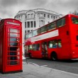London, the UK. Red phone booth and red bus in motion — Foto de Stock