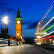 Stock Photo: London, the UK. Red bus in motion and Big Ben at night