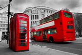 London, the UK. Red phone booth and red bus in motion — Stock Photo