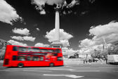 Trafalgar Square in London, the UK. Red bus, black and white — Stock Photo