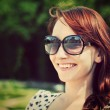 Stock Photo: Young beautiful woman in sunglasses smiling in a summer park.