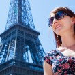 Attractive girl with Eiffel tower in the background — Stock Photo #27498821