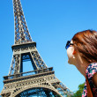 Attractive girl with Eiffel tower in the background — Stock Photo #27498985