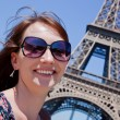 Attractive girl with Eiffel tower in the background — Stock Photo