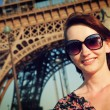 Attractive girl with Eiffel tower in the background — Stock Photo #27500063
