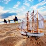 Ship model on summer beach at sunset — Stock Photo