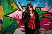 Fashionable girl and colorful graffiti wall — Stock Photo
