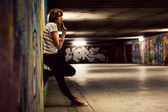 Stylish girl standing in grunge graffiti tunnel, shanty town — Stock Photo